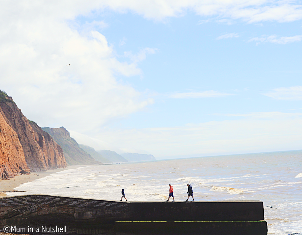 The dramatic red cliffs and sea  silhouette this  family taking walk on the pier